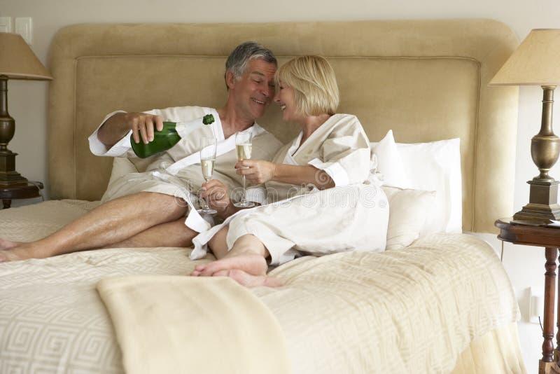 coppie invecchiate del champagne della camera da letto che godono della metà immagini stock