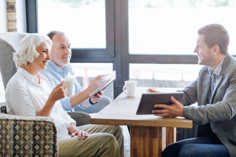 Coppie invecchiate sorridenti piacevoli che hanno riunione nel caffè fotografie stock libere da diritti