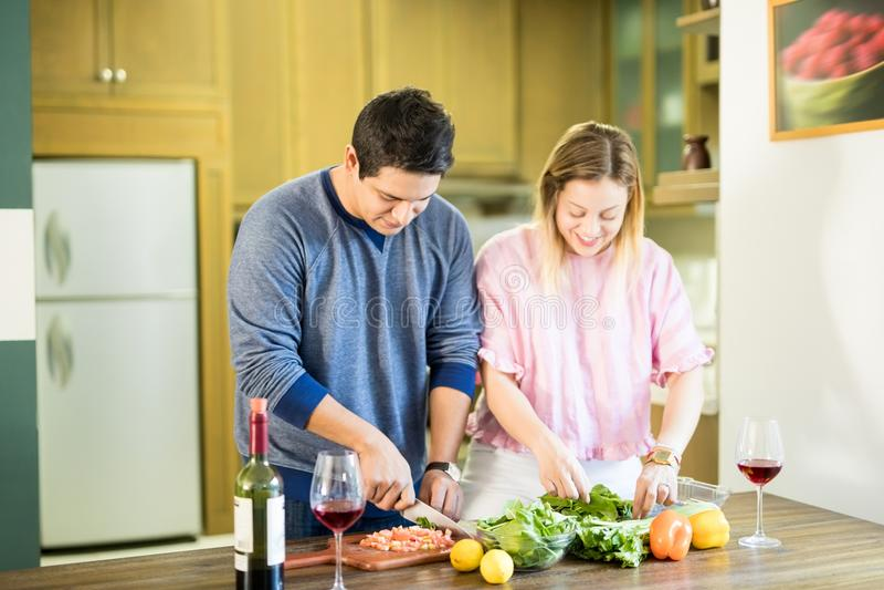 Coppie ispane che cucinano insieme a casa fotografie stock libere da diritti