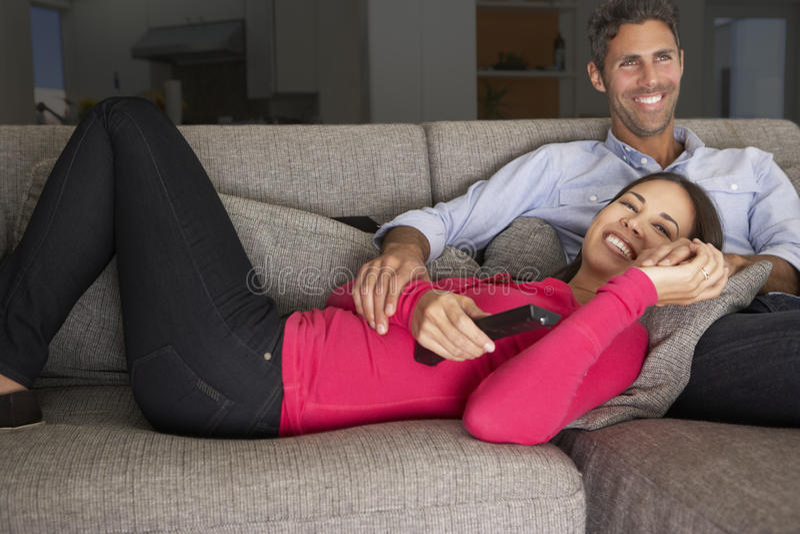 Coppie ispane su Sofa Watching TV fotografie stock libere da diritti