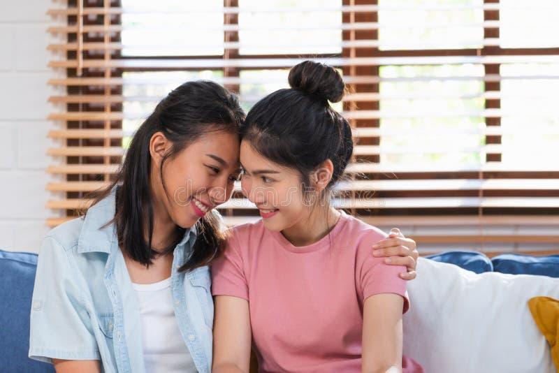 Coppie lesbiche asiatiche felici abbracciarsi con amore sul sofà al salone a casa, concetto di stile di vita di LGBTQ immagine stock libera da diritti