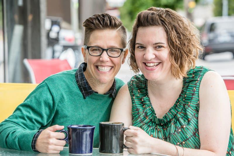 Coppie lesbiche felici che si siedono alla tavola fuori immagini stock