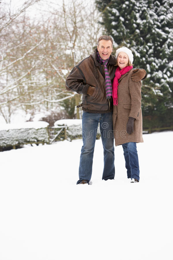 Coppie maggiori che camminano nel paesaggio dello Snowy fotografia stock