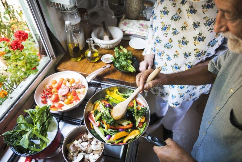 Coppie maggiori che cucinano nella cucina immagine stock