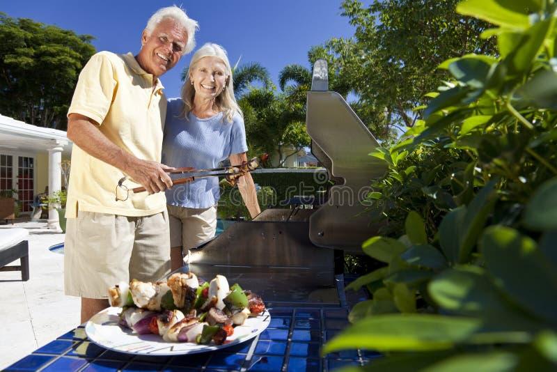 Coppie maggiori che cucinano su un barbecue di estate fotografie stock libere da diritti