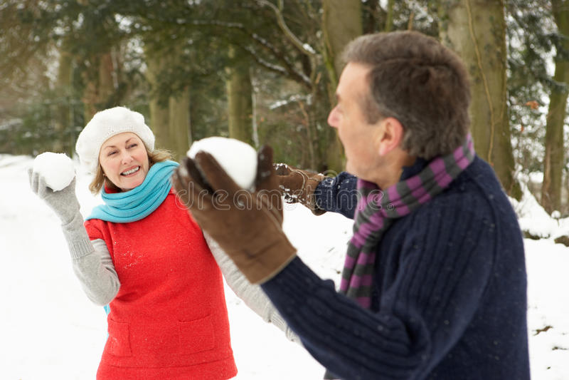 Coppie maggiori che hanno lotta della palla di neve immagine stock