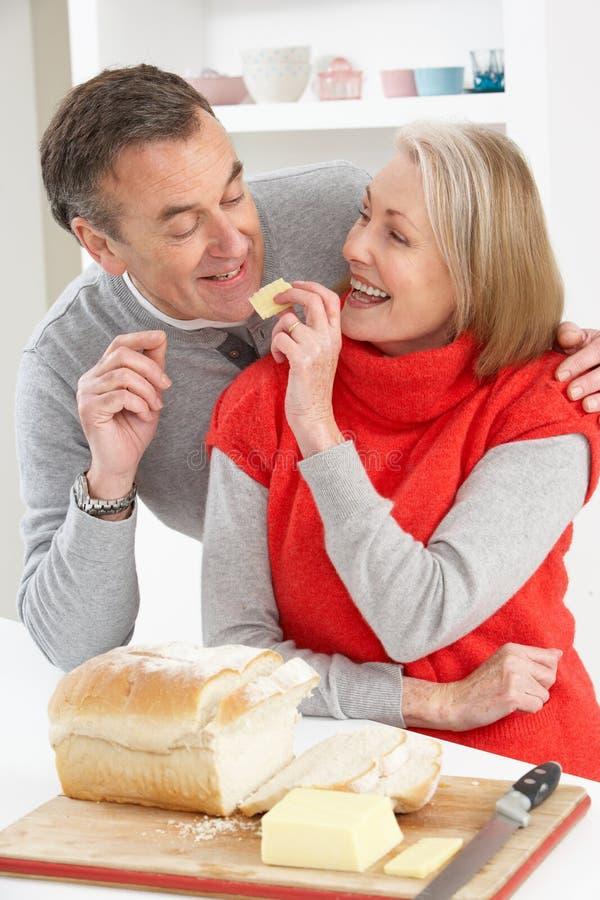 Coppie maggiori che producono panino in cucina fotografie stock libere da diritti
