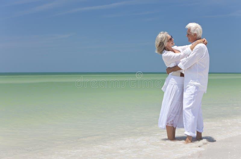 Coppie maggiori felici che abbracciano su una spiaggia tropicale fotografia stock