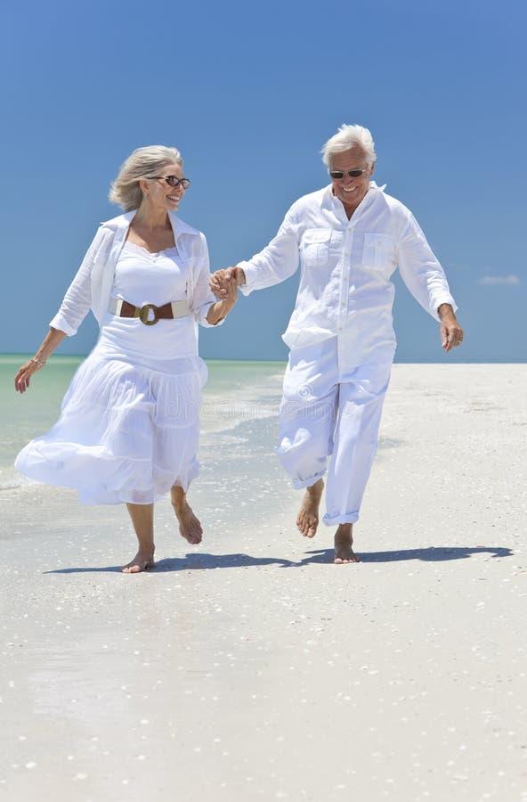 Coppie maggiori felici che funzionano su una spiaggia tropicale immagine stock