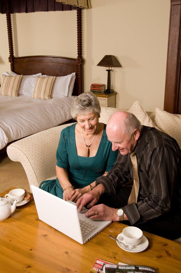 Coppie maggiori utilizzando computer portatile nella camera di albergo immagini stock