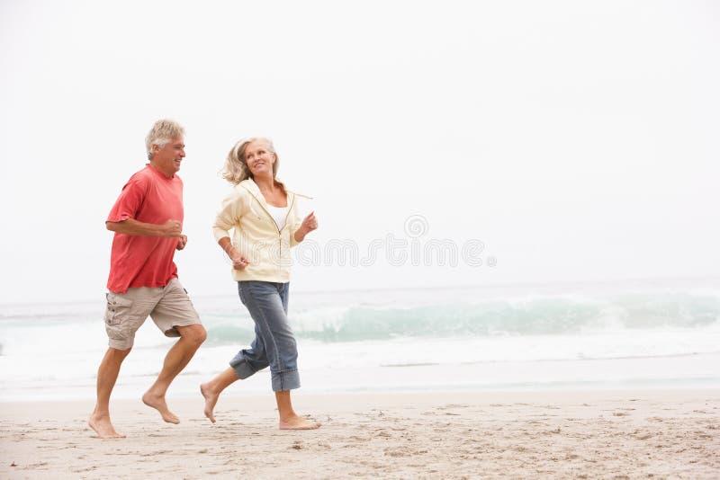 Coppie maggiori in vacanza che funziona lungo la spiaggia fotografia stock libera da diritti