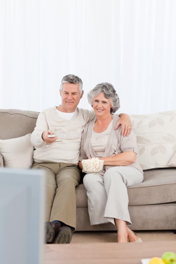 Coppie mature che guardano TV nel loro salone fotografia stock