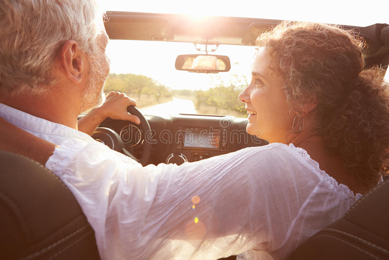 Coppie mature che guidano lungo la strada campestre in automobile senza coperchio fotografia stock libera da diritti