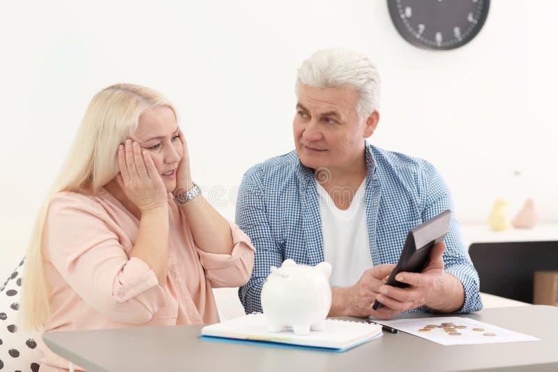 Coppie mature che pensano al pagamento di pensione a casa immagini stock