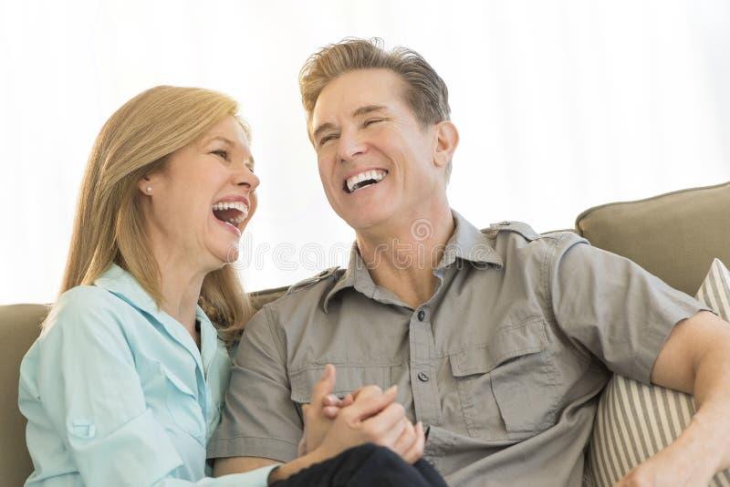 Coppie mature che ridono insieme su Sofa At Home immagini stock libere da diritti