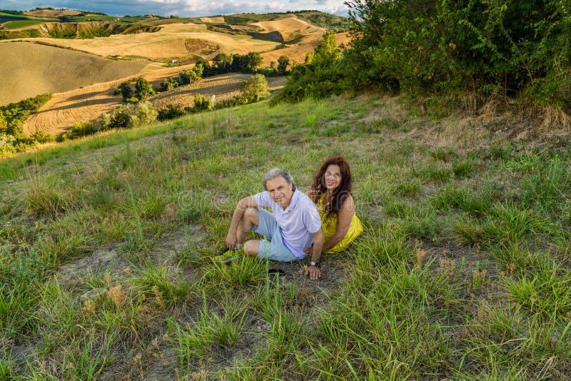 Coppie mature che si siedono nel campo erboso fotografia stock