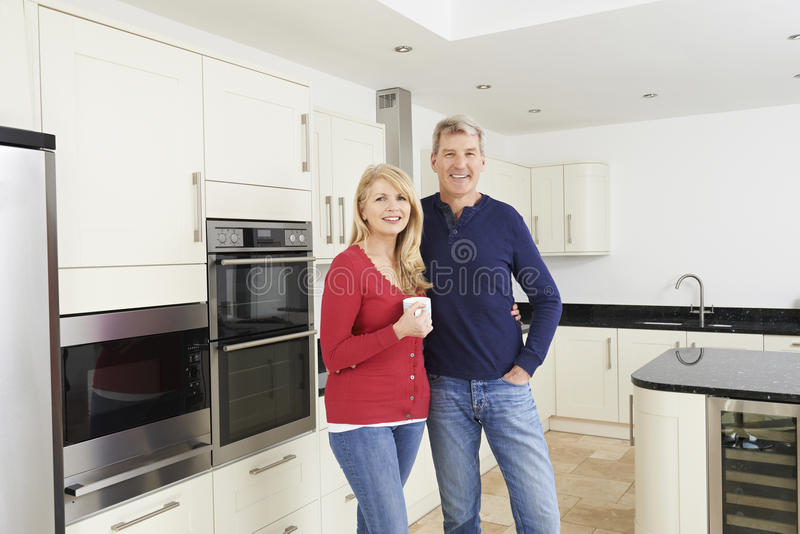 Coppie mature che stanno insieme nella bella cucina misura fotografia stock libera da diritti