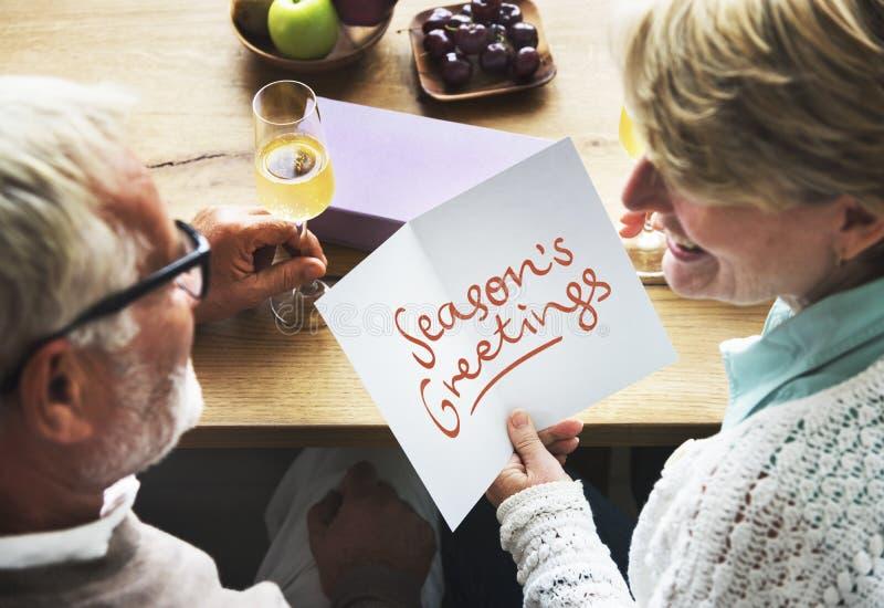 Coppie mature che tengono una cartolina d'auguri del ` s di stagione immagine stock libera da diritti