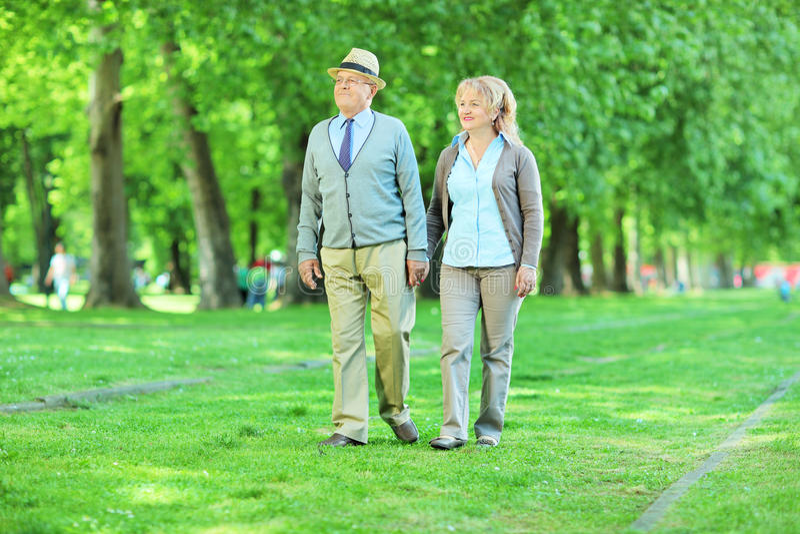 Coppie mature che vanno a fare una passeggiata in un parco fotografie stock libere da diritti
