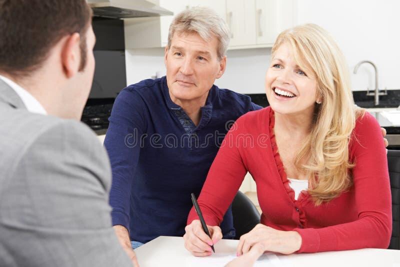 Coppie mature con il documento di firma del consulente finanziario a casa fotografia stock libera da diritti