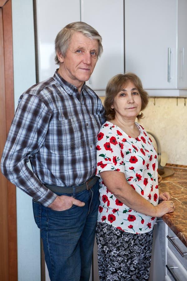Coppie mature di pensionamento positivo caucasico che stanno accanto al controsoffitto della cucina e che esaminano macchina foto fotografie stock libere da diritti