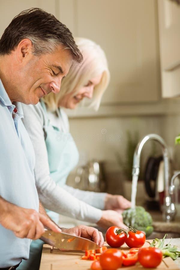 Coppie mature felici che preparano le verdure fotografia stock