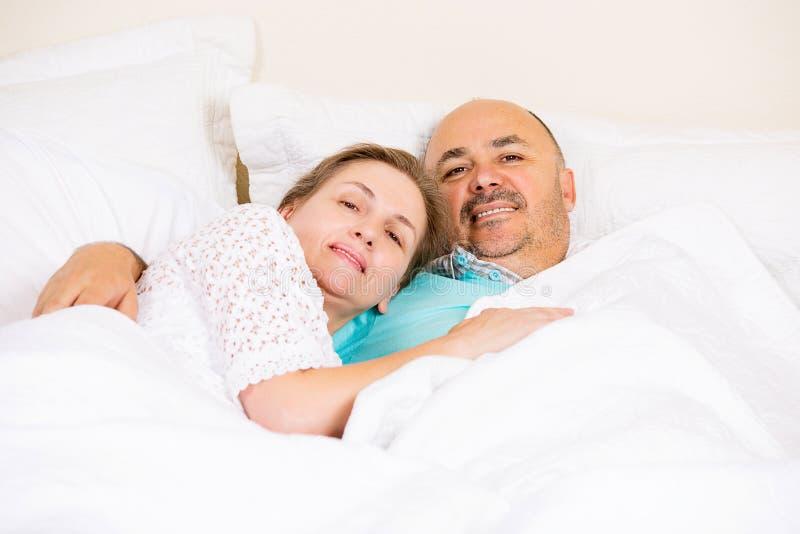 Coppie mature felici che si rilassano in un letto immagine stock
