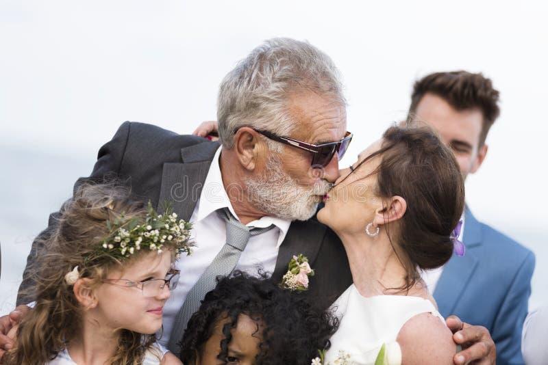 Coppie mature giovanili che si sposano alla spiaggia fotografia stock