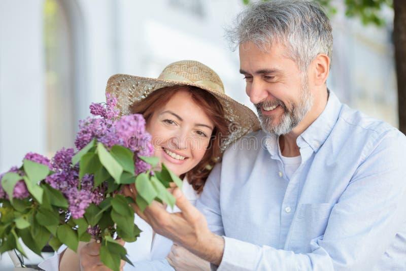 Coppie mature romantiche che camminano attraverso la citt?, uomo che d? mazzo dei fiori lilla alla sua moglie immagine stock libera da diritti