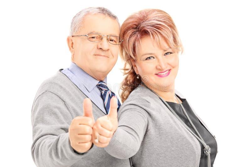 Coppie mature sorridenti che danno i pollici su immagini stock libere da diritti