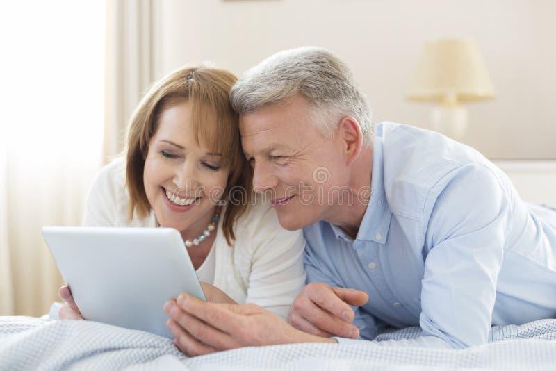 Coppie mature sorridenti che dividono compressa digitale mentre trovandosi sul letto a casa fotografie stock libere da diritti