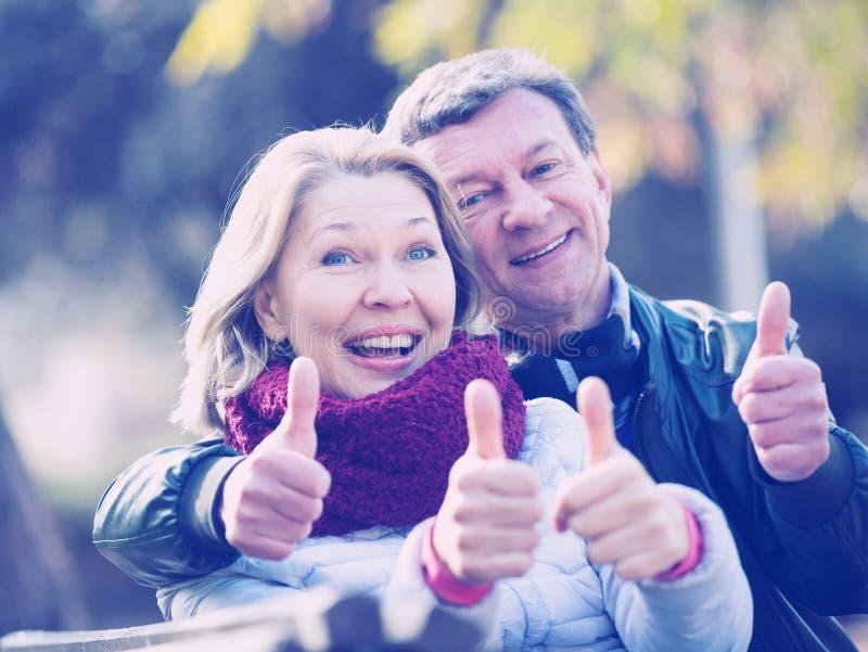 Coppie mature sorridenti che mostrano i pollici su fotografia stock