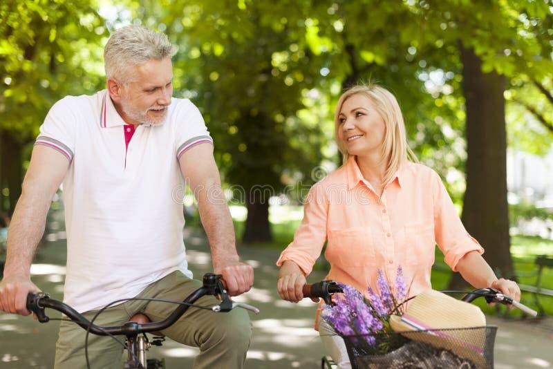 Coppie mature sulle bici all'aperto fotografia stock