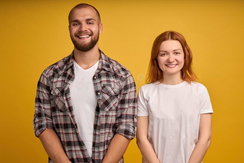 Coppie millenarie attraenti sorridenti sparate cape del ritratto dello studio nella posa di amore sulla parete gialla che esamina immagini stock
