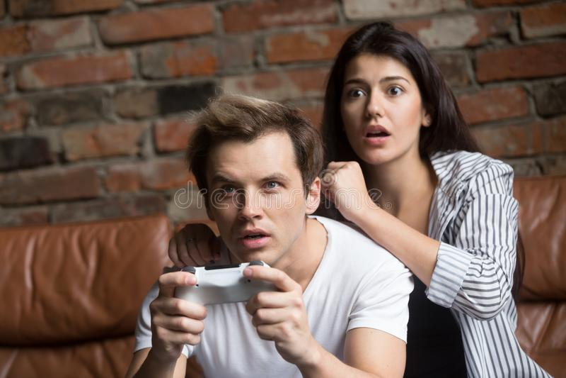 Coppie millenarie preoccupate giocando il video gioco del computer immagine stock