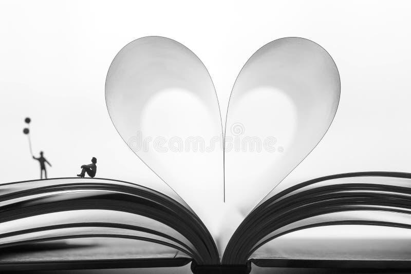 Coppie miniatura su un libro il giorno dei biglietti di S. Valentino immagine stock libera da diritti