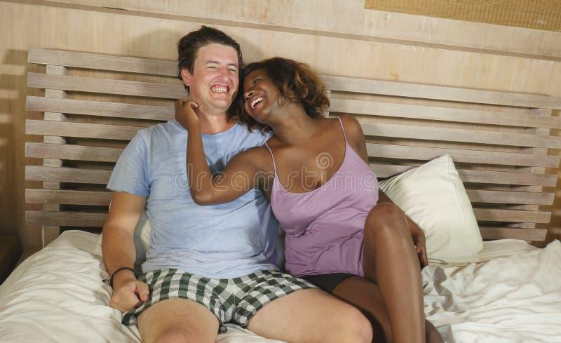 Coppie miste di etnia nell'amore che stringe a s? insieme a casa a letto con la bella amica o moglie afroamericana nera allegra e fotografie stock