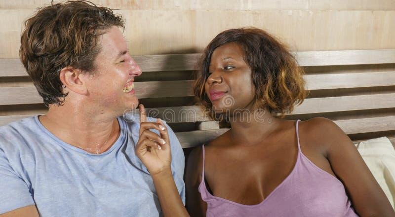 Coppie miste di etnia nell'amore che stringe a s? insieme a casa a letto con la donna americana del bello africano nero allegro e immagini stock