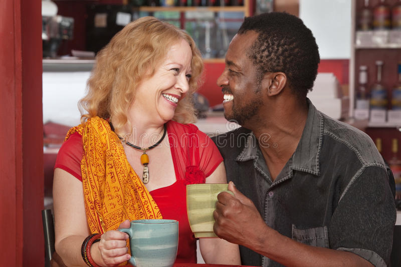 Coppie miste sorridenti che mangiano caffè fotografia stock