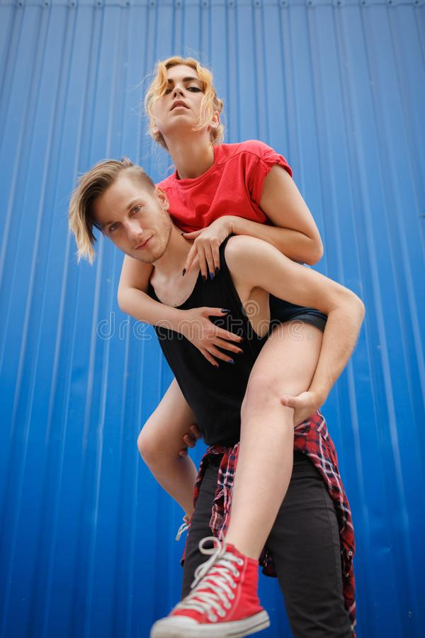 Coppie moderne ed alla moda su fondo blu, adolescenti soleggiati dei pantaloni a vita bassa delle coppie del ritratto fotografia stock libera da diritti