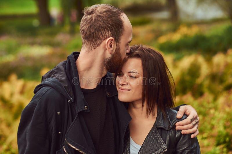 Coppie moderne felici in un parco Godere del loro amore e natura fotografie stock libere da diritti