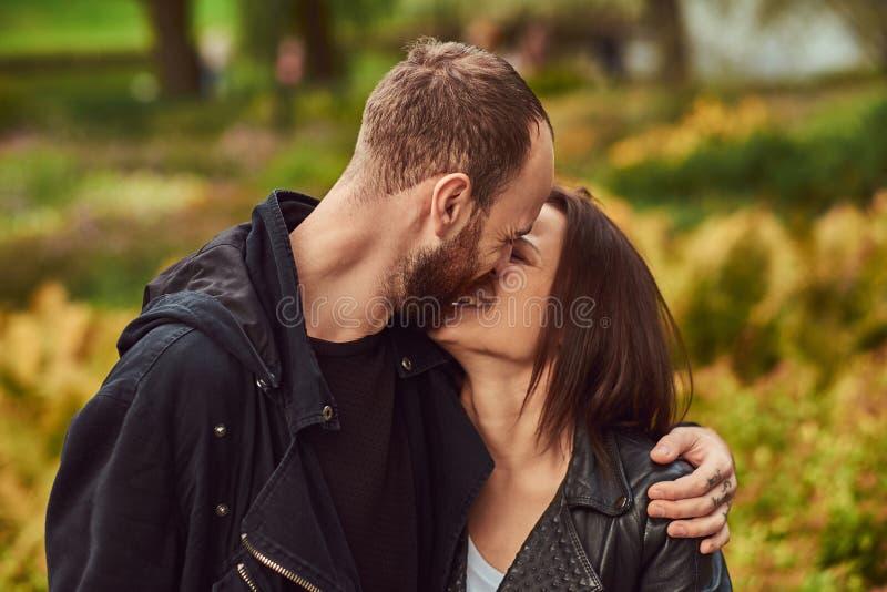 Coppie moderne felici in un parco Godere del loro amore e natura immagini stock libere da diritti