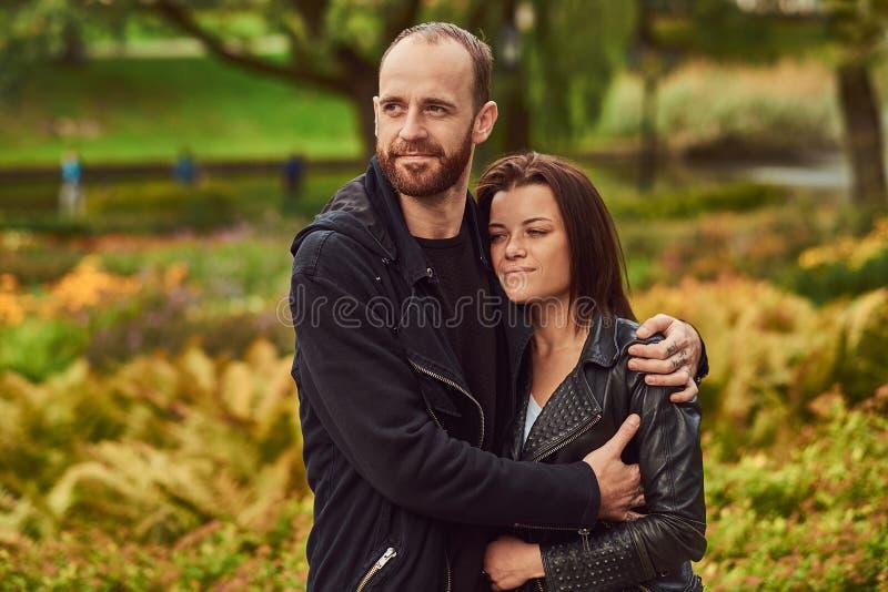 Coppie moderne felici in un parco Godere del loro amore e natura fotografie stock