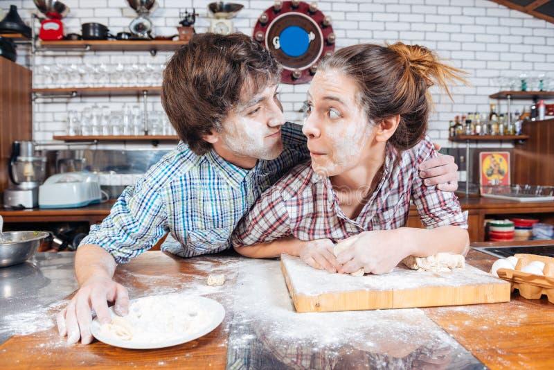 Coppie in modo divertente che fanno insieme i fronti divertenti sulla cucina fotografia stock libera da diritti