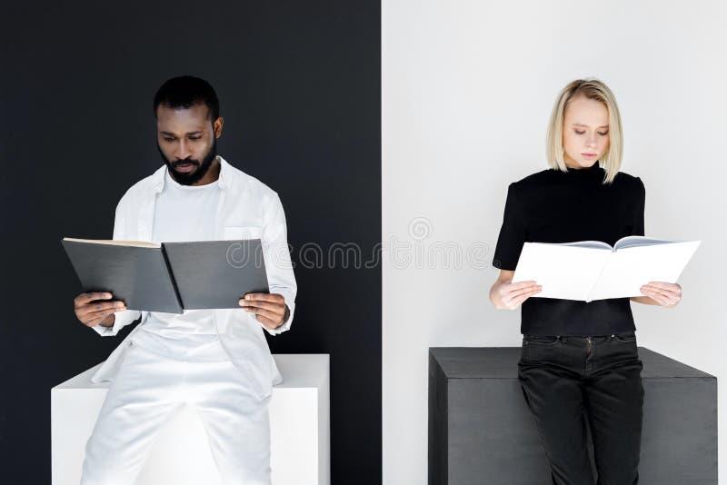 coppie multiculturali che leggono il yin in bianco e nero dei libri fotografia stock