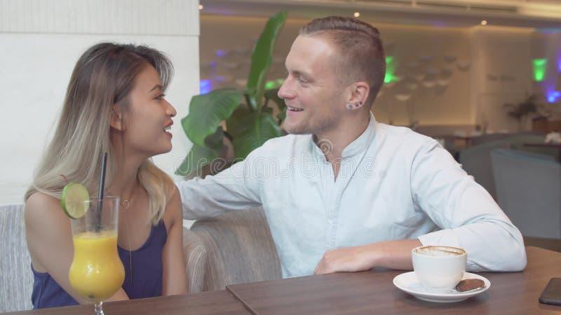 Coppie multiculturali che parlano l'un l'altro Uomo caucasico, donna asiatica alla data fotografia stock