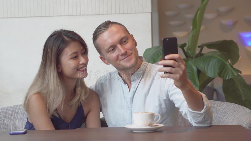 Coppie multiculturali che prendono autoritratto facendo uso dello smartphone immagini stock