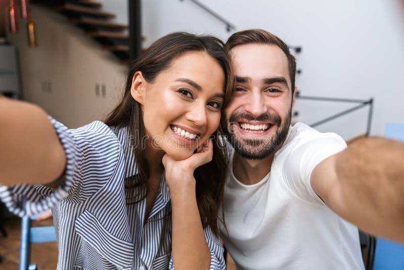 Coppie multietniche allegre che prendono un selfie fotografia stock