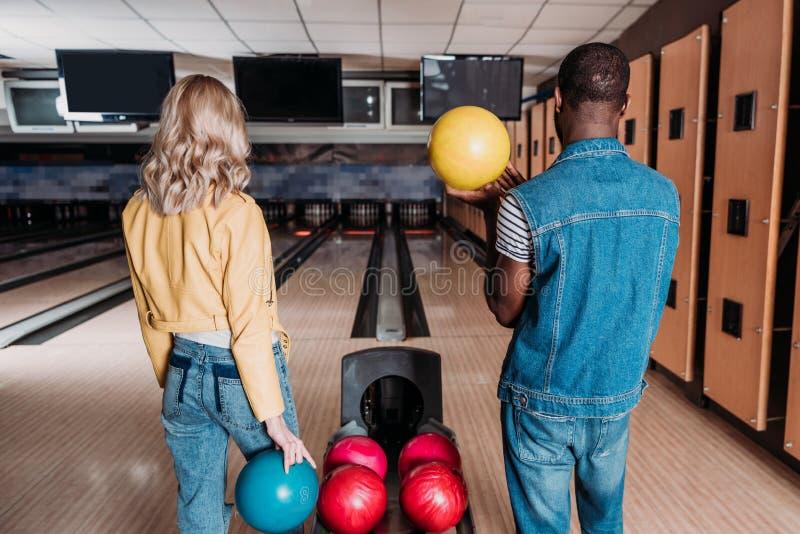 coppie multietniche con le palle da bowling che stanno davanti ai vicoli immagini stock