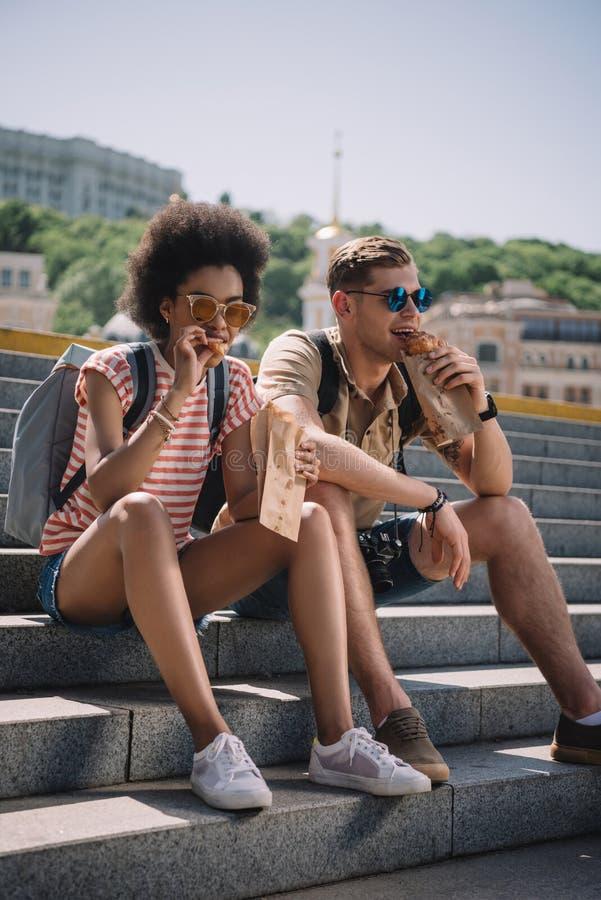 coppie multietniche dei viaggiatori che si siedono sulle scale e sul cibo fotografia stock